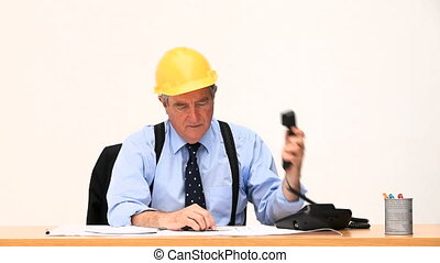 Senior businessman making a phone call at his desk