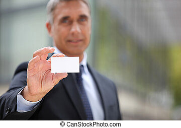 Senior businessman offering business card