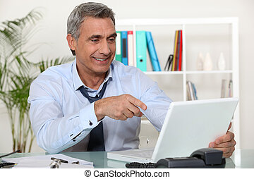 Senior businessman pointing at laptop