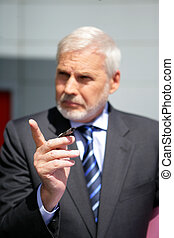 Senior businessman pointing his finger