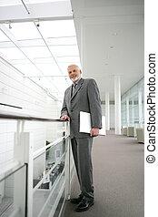 Senior businessman posing in the corridor