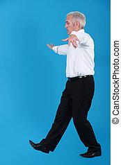 senior businessman pretending to walk on wire