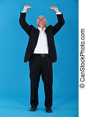 Senior businessman pushing upwards