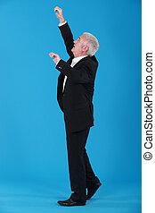 Senior businessman reaching upwards