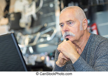 senior businessman reading information on the screen