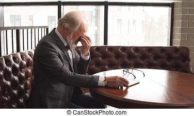 Senior businessman rubbing his tired eyes.