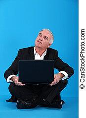 Senior businessman sat on the floor with laptop