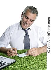 senior businessman sign check green grass