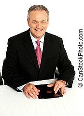 Senior businessman sitting with tablet on desk
