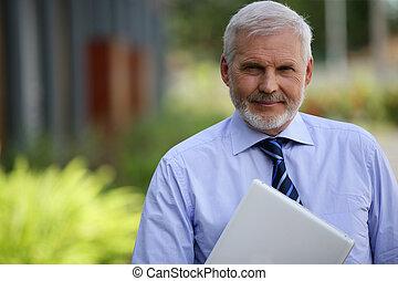 Senior businessman stood outdoors with laptop