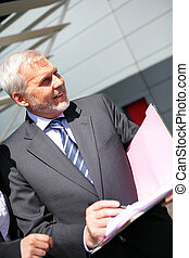 Senior businessman stood outside corporate building