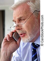Senior businessman taking a call outdoors