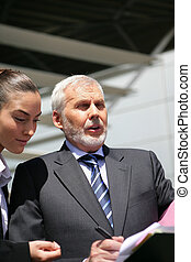 Senior businessman talking to a young woman