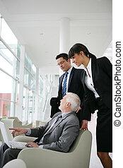 senior businessman talking to his assistants