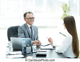 senior businessman talking to his young assistant at the Desk
