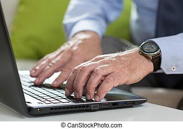 Senior businessman uses laptop for work