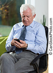 Senior businessman using phone