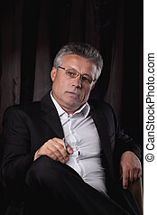 senior businessman with a cigarette,sitting in a chair