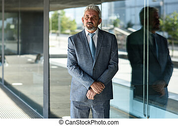 Senior businessman with arms crossed outside of modern office building.