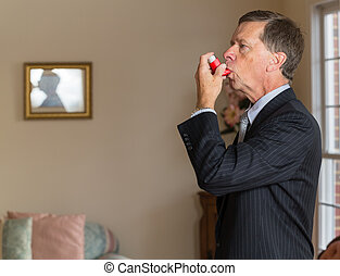 Senior businessman with asthma inhaler