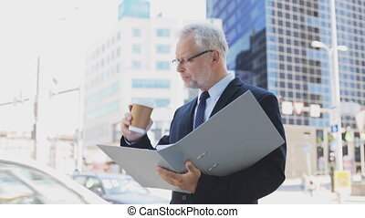 senior businessman with coffee and folder in city -...