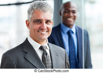 senior businessman with colleague on background