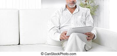 senior businessman with digital tablet sitting on sofa