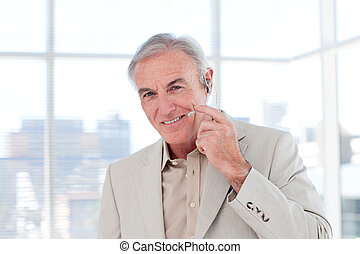 Senior businessman with headset on smiling at the camera
