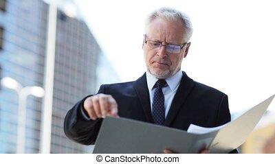 senior businessman with ring binder folder in city -...
