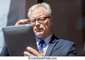 senior businessman with tablet pc on city street