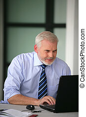 Senior businessman working-away at his desk