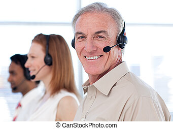 Senior businessman working in a call center with his...