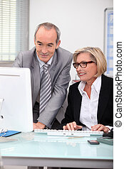 Senior businesspeople in front of laptop computer