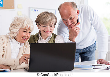 Senior businesspeople with laptop