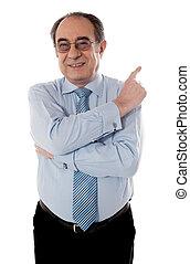 Senior businessperson pointing away
