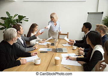 Senior businesswoman handing financial report to manager at team