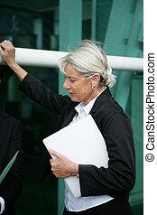 Senior businesswoman leaning against structure