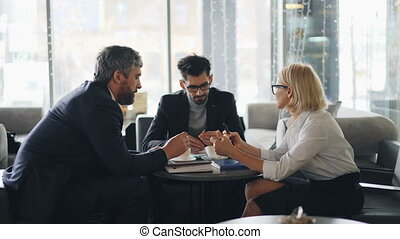 Senior businesswoman making business offer to partners in cafe talking gesturing