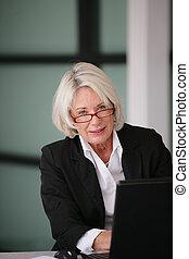 Senior businesswoman sending e-mails
