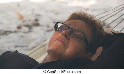 senior businesswoman sleeping in hammock closeup
