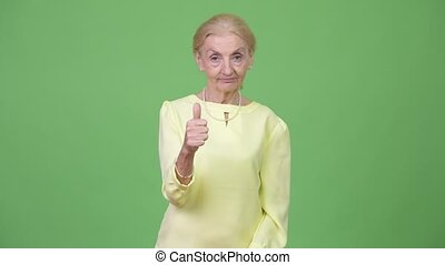 Senior businesswoman with blond hair giving thumbs up