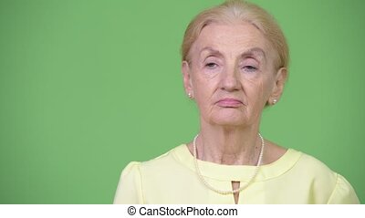 Senior businesswoman with blond hair thinking against green...