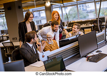Senior businesswoman working together with young business people in modern office