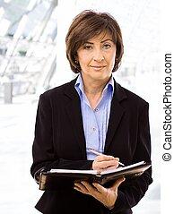 Senior businesswoman writing