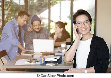 Senior businesswomen using smart phones and smiling at camera in office