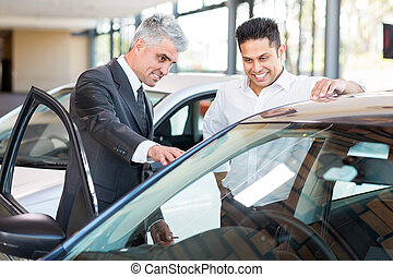 car salesman showing a new car to customer