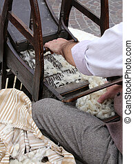 Senior carder while carding wool or cotton with old wooden machi