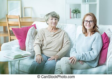 Senior care assistant sitting with elderly patient