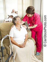 Senior Care in Nursing Home - Nurse cares for an elderly...