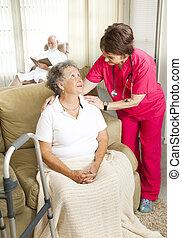 Nurse cares for an elderly woman in a nursing home.